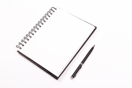 Spiral notepad and a pen on white background. Stationery concept. Flat-lay, top view. Banque d'images