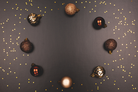 Holiday composition made with Christmas balls and confetti. Wreath on black background. Dark and moody toning Flat lay, top view, copy space.
