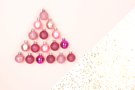 Christmas tree made from decor on white and pink combination background. Holiday and New Year concept. Flat-lay, top view. Copy space for text.