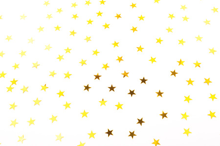 Golden star shaped confetti on white background. Holiday, festive and New Year concept.Flat-lay, top view.