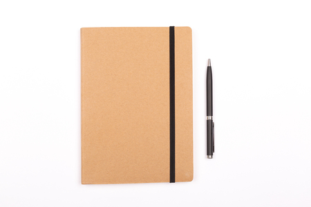 Closed notepad and a pen on white background. Stationery concept. Flat-lay, top view.