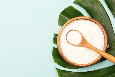 Kollagenpulver in Schüssel und Messlöffel auf Palmblatthintergrund. Zusätzliche Proteinzufuhr. Natürliche Schönheits- und Gesundheitsergänzung. Kollagenkonzept auf pflanzlicher Basis. Flatlay, Ansicht von oben. Platz kopieren. Standard-Bild