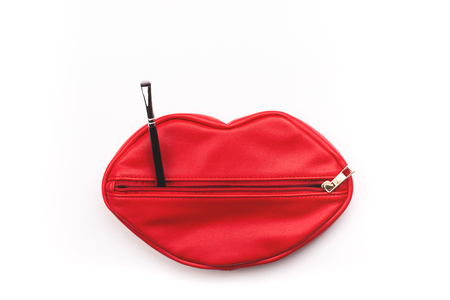 Makeup bag in red lips shape and brush on white background. Creative beauty and cosmetics concept. Stock Photo