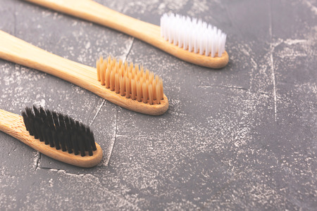 Three bamboo tooth brushes on grey background. Zero waste and plastic free concept. Copy space for your text.