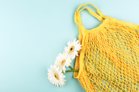 Yellow eco bag and three gerberas on light green background. Eco, zero waste and plastic free concept. Flat lay, top view. Copy space for your text.