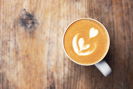 A beautiful cup of cappuccino with latte art in the wooden space background. Trendy toning. Minimal composition, hipster vibes. Top view, flat lay. Copy space for your text. Stock fotó
