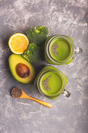 Two green smoothies, greens, vegetable and fruits on moody background. Healthy eating, diet and vegetarian concept. Vertical shot. Copy space for your text.