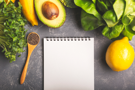 Diet, nutritoon plan, shopping list or recipe concept. Greens, spinach, avocado, banana and lemon on moody background. Healthy eating, diet and vegetarian. Horizontal shot. Copy space for your text.