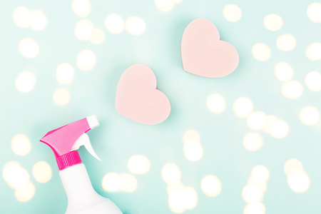 Spring cleaning concept. Spray and heart shape sponges on light green background. Trendy toning. Flat lay, top view. Copy space for your text.