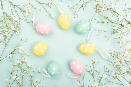 Hand painted Easter eggs on floral background. April holiday concept. Flat lay, top view. Copy space for your text.