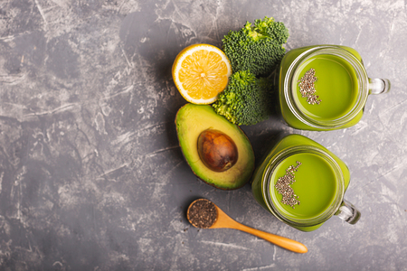 Two green smoothies, greens, vegetable and fruits on moody background. Healthy eating, diet and vegetarian concept. Horizontal shot. Copy space for your text. Stock fotó