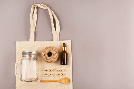 Zero waste background. Cotton shopping bag, glass jars, bamboo toothbrushes. Plascic free concept. Flat lay, top view.