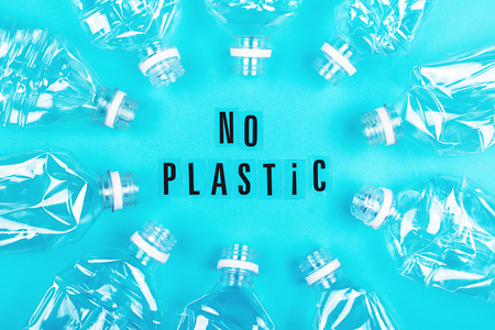 Plastic free and zero waste concept. Many empty plastic bottles on blue background and no plastic letters. Flat-lay, top view.