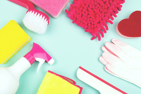 Frame made of spring cleaning products on light green background. Cleaning tools for various areas: kitchen, balcony and windows, bathroom toilet. Copy space for your text.