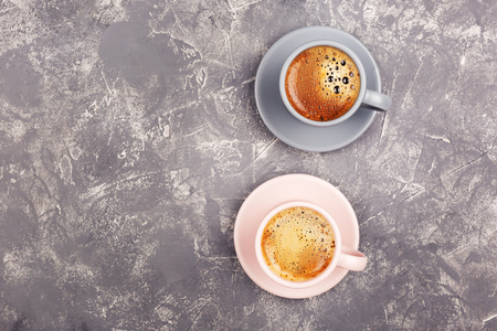 Two cups of coffee with tasty froth on grey background. Flat lay, top view. Copy space for your text.