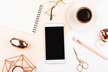 Creative feminine workspace background. Smartphone, notepad, glasses, coffee. Flat-lay, top view. Copy space for your text. Stock fotó