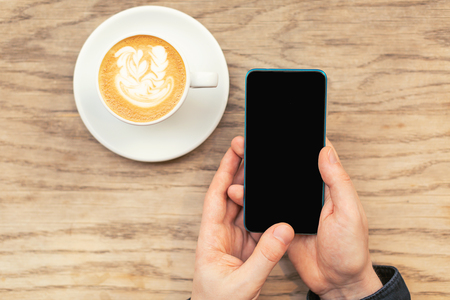 A man is holding a cellphone in hands and a cup of coffee. Flat lay, top view. Copy space for your text.