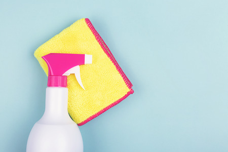 Spring cleaning products on light green background. Spray and cleaning rag. Minimal composition. Copy space for your text.