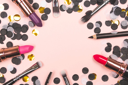 Makeup and beauty background. Frame made with different products and tools such as brushes and lipsticks. Flat lay, top view. Copy space for your text. Horizintal shot.