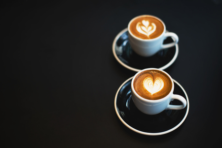 Two elegant cups of espresso macchiato on the black table. Beautiful heart shape latte art. Coffee love concept. Flat-lay, top view. Copy space for your text. Stock fotó