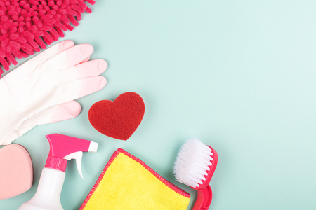 Spring cleaning products on light green background. Cleaning tools for various areas: kitchen, balcony and windows, bathroom toilet. Copy space for your text.