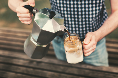 Ice coffee concept. A man pouring coffee from a coffee maker to a jar with milk and ice. Outdoor shot. Lifestyle, picnic vibes. Stock fotó