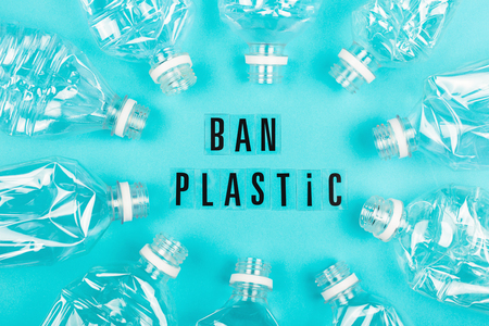 Plastic free and zero waste concept. Many empty plastic bottles on blue background and ban plastic letters. Flat-lay, top view.