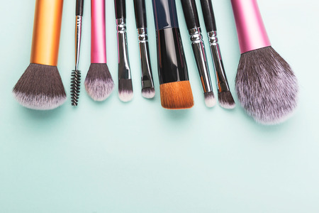 Set of makeup brushes. Beauty concept. Top view, copy space. Light green background. Stok Fotoğraf - 123439956