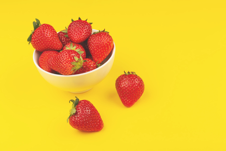 A bowl full of ripe strawberries on yellow background. Eat fruits and berries concept. Copy space.