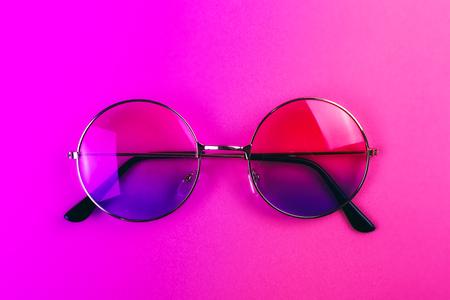 Round summer sunglasses on neon duotone light. Trendy background.
