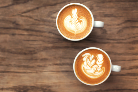 Two Beautiful cups of flat white coffee with latte art on wood table. Soft focus. Stok Fotoğraf - 123440006