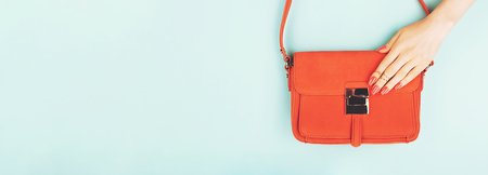 Woman hand with perfect coral manicure on trendy fashion bag. Blue background. Web banner. Copy space for your text. Stock fotó