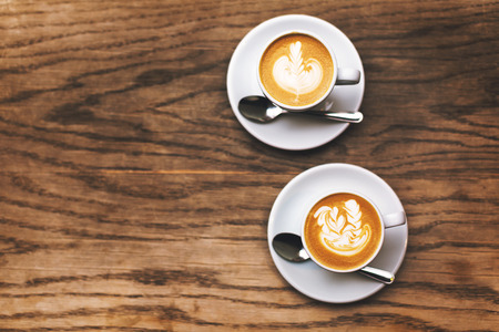 Two Beautiful cups of flat white coffee with latte art on wood table. Soft focus. Stok Fotoğraf - 123440021