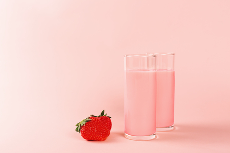 Two glasses with strawberry milk on pink background. Minimal composition.