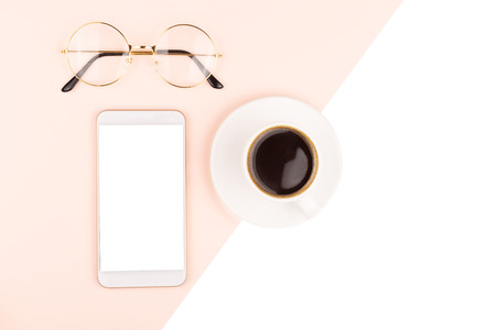 A cup of coffee, smartphone and eye glasses. Freelance, business concept. Flat lay, top view. Copy space for your text.