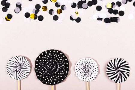 Party accessories on grey background. Cake toppers and confetti. Holiday, celebration, Birthday or Black Friday concept. Flat lay, top view. Copy space.
