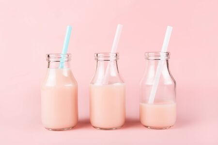Three bottles of drink on pink background. Pik yogurt, strawberry milk, smoothie or other beverage. Full, half drinked and almoust finished.