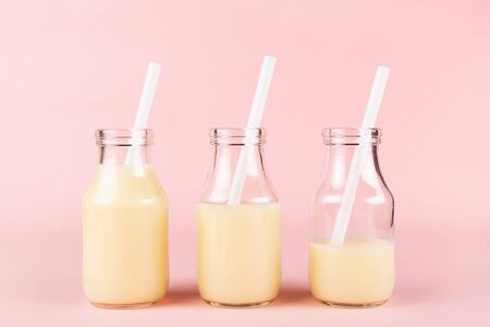 Creative shot of three bottles of drink on pink background. Banana or mango yogurt, milk, smoothie or other beverage. Copy space for your text.