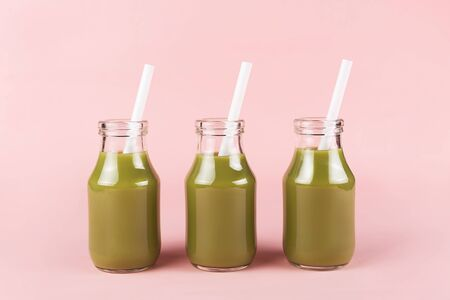 Creative shot of three bottles of vegetable drinks on pink background. Smoothies, shakes, yogurt.