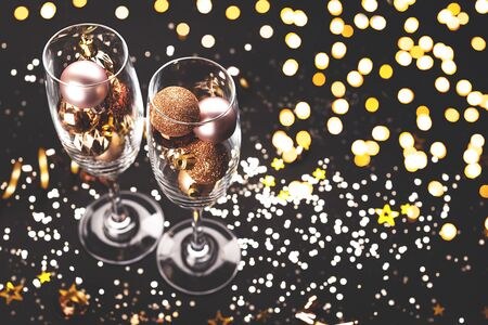 New Year composition with two glasses, decoration and lights. Holiday and celebration concept.