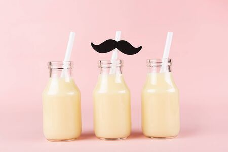 Three bottles of drink on pink background. Banana or mango yogurt, milk, smoothie or other beverage. Copy space for your text. Stock fotó