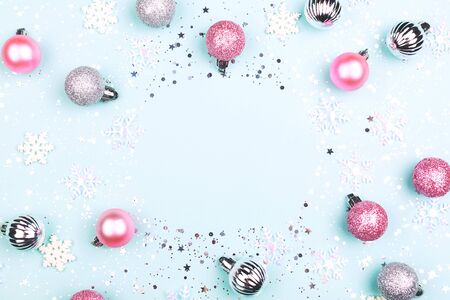 Christmas or New Year composition on turquoise background. Decoration, snow flakes and glitter. Holiday concept. Flat-lay top view. Copy space for your text.