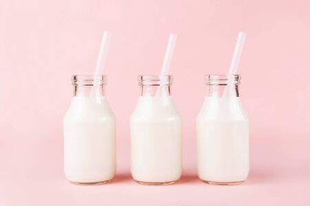 Creative shot of three bottles of milk of yogurt on pink background.