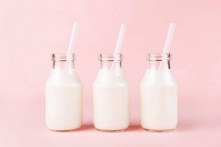 Tiro creativo de tres botellas de leche de yogur sobre fondo rosa. Foto de archivo