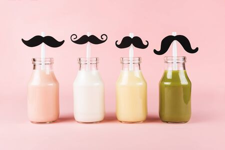 Four bottles of colorful drinks with cute straws on pink background. Smoothies, shakes, yogurt.
