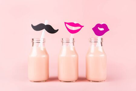 Three bottles of drink with funny straws on pink background. Pik yogurt, strawberry milk, smoothie or other beverage.