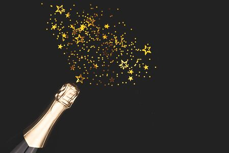 Creative New Year composition with champagne bottle and exploding gold star shape confetti. Celebration and party concept.