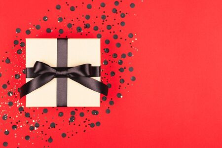 Gift box with black ribbon on vivid red background. Black Friday concept. Flat lay, top view. Minimal composition. Stock fotó
