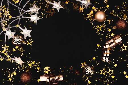 A Christmas frame made with decor, confetti and lights. Flatlay, top view. Copy space.