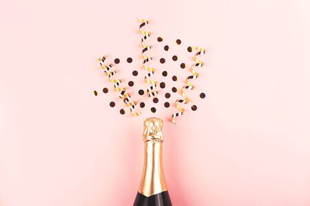 Creative New Year composition with champagne bottle and exploding gold confetti and streamers. Celebration and party concept.
